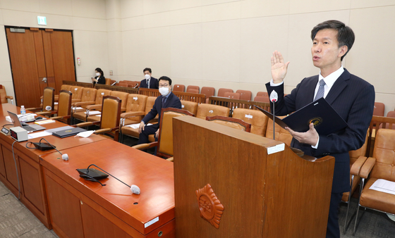 Kim Dae-ji, nominee for the National Tax Service head, undergoes a sworn ceremony before his confirmation hearing on Wednesday. Seats for lawmakers' aides and journalists are nearly empty to maintain the elevated preventive measures.  [YONHAP]
