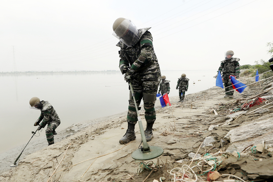 At an estuary of Imjin River in Gimpo, Gyeonggi, on Thursday, marines in protective gear search for land mines that may have washed downstream from North Korea by recent torrential rainfall and flooding.  [YONHAP]