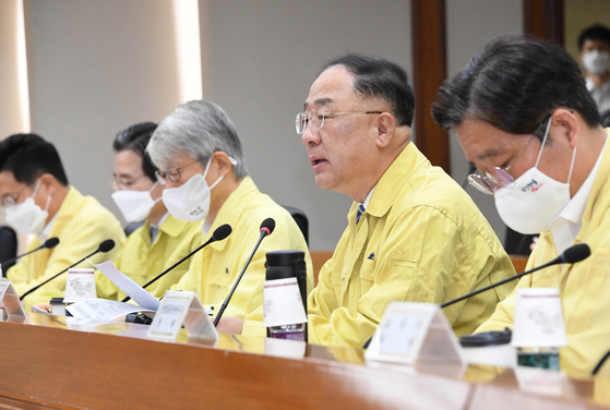 FInance Minister Hong Nam-ki, second from right, attends an emergency meeting in Seoul on Thrusday. On his Facebook post, Hong emphasized the narrowing income gap between the poor and the rich. [YONHAP]