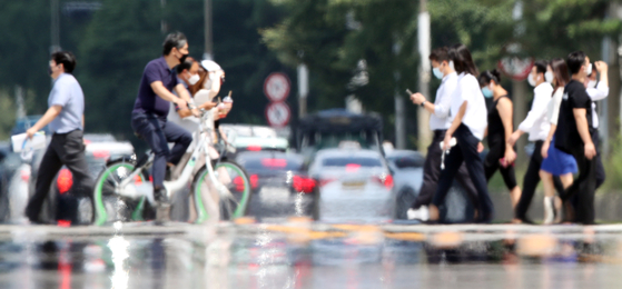 Pedestrians walk on an asphalt road in Yeouido, western Seoul. Heat shimmers from the surface as daytime temperatures in Seoul rise above 34 degrees Celsius (93.2 degrees Fahrenheit) on Thursday.  [YONHAP]