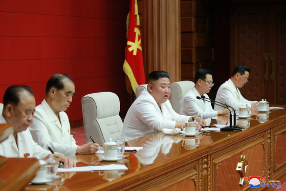 North Korean leader Kim Jong-un, center, speaks at a plenary meeting of the ruling Workers' Party Central Committee on Wednesday, during which he announced a new party congress to be held next January. [YONHAP]