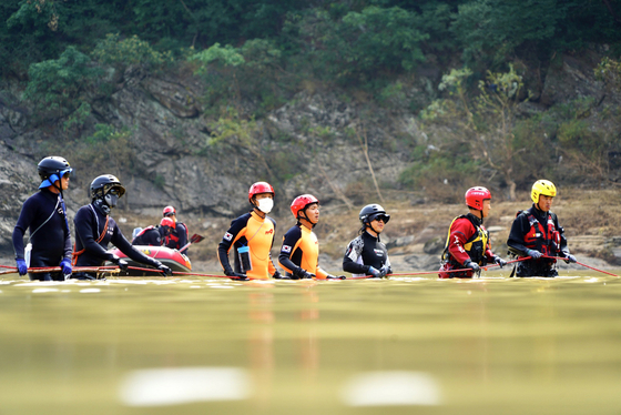 A joint search team of firefighters, police and soldiers comb through the Bukhan River in Chuncheon, Gangwon, on Thursday in search of two missing people. Three boats were overturned amid rapidly flowing floodwaters near the Euiam Dam on Aug. 6. Seven people aboard the three vessels went missing. One was rescued alive and four were found dead. [YONHAP]