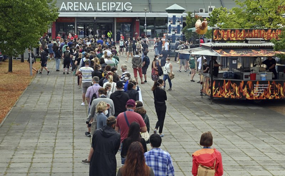"Test participants at a large-scale experiment by the University Medicine Halle/Saale stand at the entrance to the Arena Leipzig in Germany on Aug. 22. Around 2,200 visitors took part in the experiment, titled ""Restart-19,"" in which pop singer Tim Bendzko performed. [AP/YONHAP]"