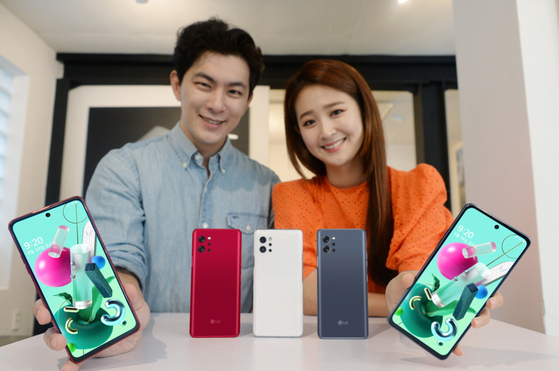 Models display LG Electronics' Q92, a 5G-enabled smartphone with a relatively low price tag of 499,400 won ($420), on Sunday. It features a 48-megapixel main camera, an 8-megapixel ultrawide lens, a 5-megapixel depth sensor and a 2-megapixel macro lens. On the front, it comes with a 32-megapixel selfie camera. [YONHAP]