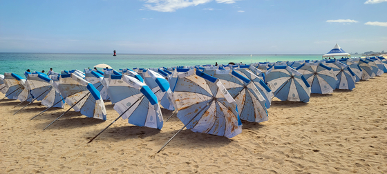 Parasols are laid down to be dried on Gyeongpo Beach in Gangneung, Gangwon, on Sunday as all business activities on beaches across the nation were ordered to shut down Sunday amid a surge in Covid-19 cases. [YONHAP]