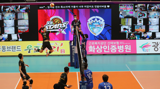 Volleyball teams for KB Insurance and Samsung Fire Insurance play a game without fans in the stands in Jecheon Gymnasium in North Chungcheong on Monday, with a spike in new coronavirus cases prompting tighter social distancing standards. Instead, multiple monitors in the stands show fans watching the game through a live-streaming service. [YONHAP]