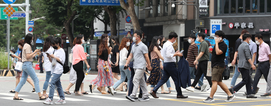 Pedestrians cross a road in central Seoul while wearing face masks Monday, the first day that the Seoul Metropolitan Government's face mask order went into effect. [NEWS1]