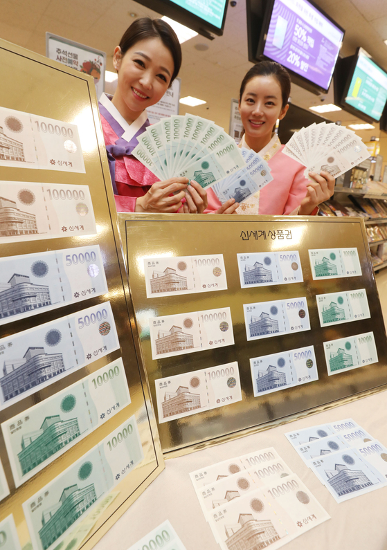 Models promote Shinsegae Department Store gift certificates at Emart's Seongsu branch in eastern Seoul on Monday, ahead of the Chuseok harvest festival. Emart sells the gift certificates in its branches across the country and provides additional certificates for people who buy those worth over 10 million won ($8,420). [YONHAP]