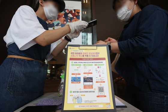 A worker at a coffee shop in Seoul scans a customer's QR code on Monday as part of track-and-trace measures. [YONHAP]