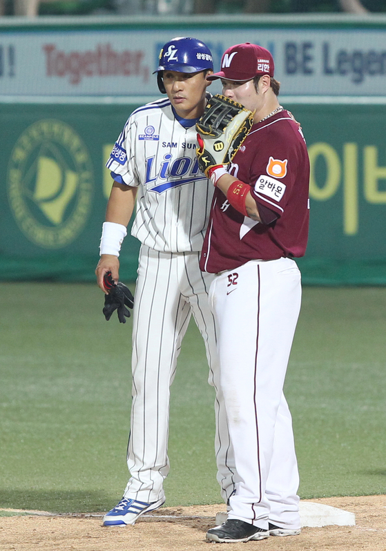 Fomer Samsung Lions slugger Lee Seung-yuop, left, and Park Byung-ho of the Kiwoom Heroes talk to each other during a KBO game back in June 24, 2014. [ILGAN SPORTS]