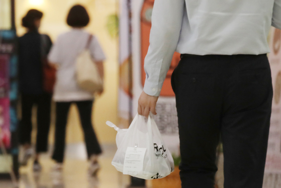 An office worker walks with takeout in downtown Seoul on Tuesday. As the resurgence of the coronavirus started around Aug. 15, takeout orders by office workers during lunch have spiked with people avoiding restaurants and cafes. [YONHAP]