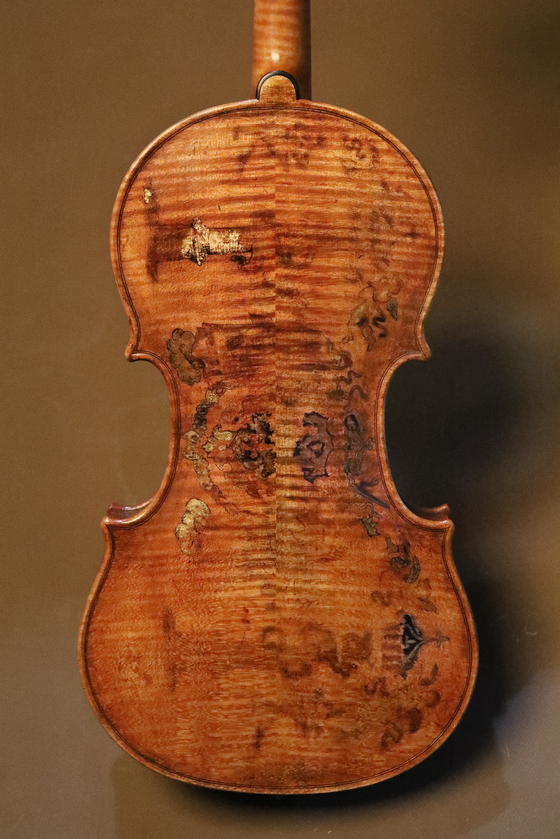 After reproducing a violin made by world-famous luthier Andrea Amati, Kim draws on the back and ribs of the violin. [PARK SANG-MOON]