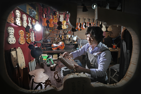 Luthier Kim Sin-seok works on making fusion musical instruments at his studio Shema String, located in Seocho-dong, southern Seoul. [PARK SANG-MOON]