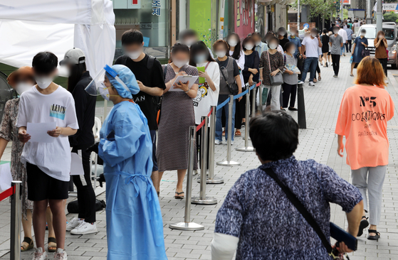 People wait to get tested at a Covid-19 testing site in Seongbuk District, central Seoul, Monday, amid a growing cluster from a church nearby. [NEWS1]