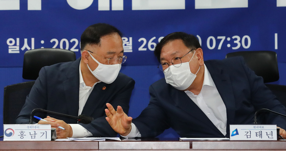 From left, Finance Minister Hong Nam-ki and Democratic Party floor leader Kim Tae-nyeon discuss next year's budget at the National Assembly in Seoul on Wednesday. [YONHAP]