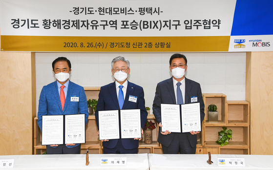 From left, Pyeongtaek Mayor Jung Jang-seon, Gyeonggi Governor Lee Jae-myung and Hyundai Mobis President and CEO Park Chung-kook pose after signing a memorandum of understanding at the Gyeonggi Provincial Government in Suwon, Gyeonggi, Wednesday. [HYUNDAI MOBIS]
