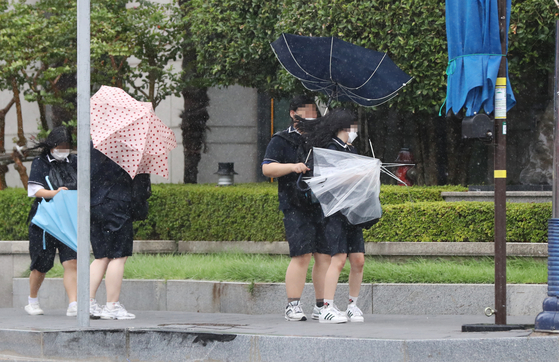 Students struggle with umbrellas in front of Mokpo Station in South Jeolla on Wednesday afternoon as Typhoon Bavi approached the peninsula. [YONHAP]