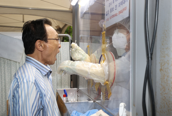 Chairman Lee Hae-chan of the ruling Democratic Party (DP) takes a coronavirus test at the Yeongdeungpo Health Office on Thursday. The National Assembly was shut down Thursday after a photojournalist who covered the ruling party's leadership meeting on Wednesday tested positive.  [YONHAP]