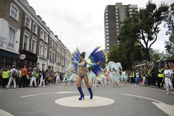 FILE - In this Monday, Aug. 27, 2018 file photo, costumed revellers perform in the parade during the Notting Hill Carnival in London. London's Notting Hill Carnival traces its roots to the emancipation of Black slaves and race riots in the city during the late 1950s. Organizers say the event is more important than ever amid the worldwide campaign for justice following the death of George Floyd in police custody. But their message of resistance and reconciliation will be delivered online worldwide this weekend after the COVID-19 pandemic forced the party to reinvent itself as a virtual event. [AP/YONHAP]