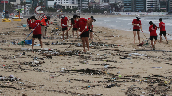 Officials of Suyeong District Office in Busan clean up Gwangalli Beach on Thursday morning after Typhoon Bavi passed. [SONG BONG-GEUN]