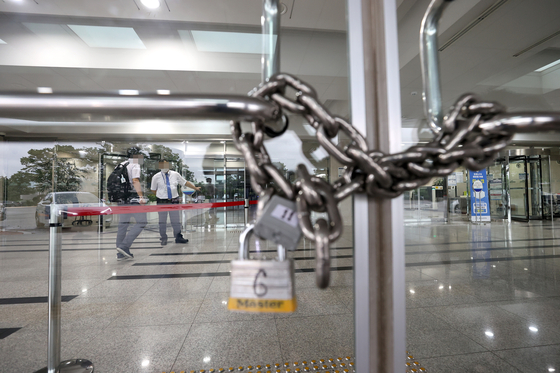 A gate at the National Assembly's main building is locked after the legislature shut its key buildings after a photojournalist covering the Democratic Party was confirmed infected with Covid-19.  [YONHAP]