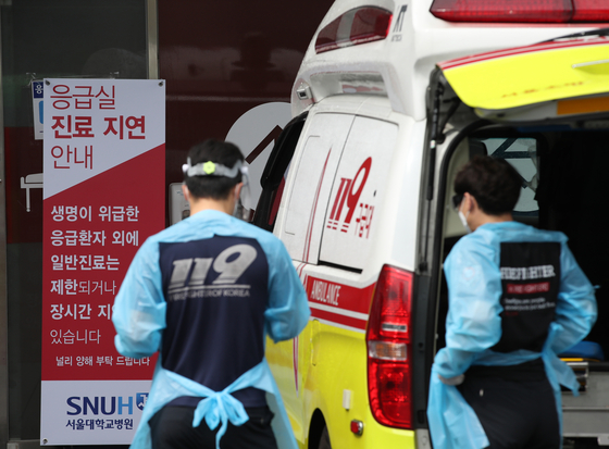 Emergency medical staff behind an ambulance parked at Seoul National University Hospital in central Seoul on Friday, the third day of a nationwide doctors' strike. [YONHAP]