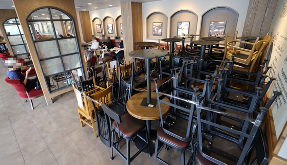 Chairs and tables are stacked up at a coffee shop in central Seoul on Friday afternoon amid social distancing measures. Starting Saturday midnight, all coffee shop chains in the Seoul metropolitan area will only offer take-out services till Sept. 6 midnight. [YONHAP]