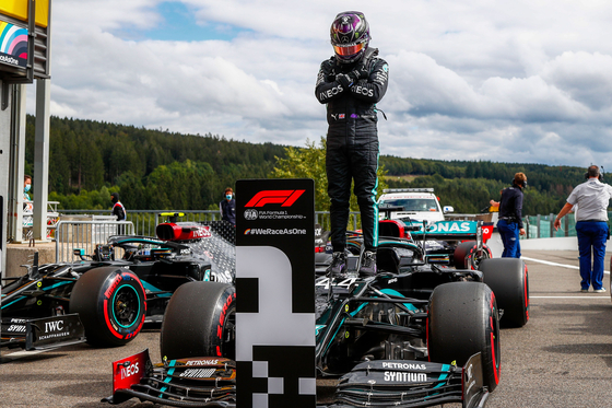 Mercedes' British driver Lewis Hamilton gestures in homage to late U.S. actor Chadwick Boseman, as he stands on his car after securing his 93rd pole position during the qualifying session at the Spa-Francorchamps circuit in Spa on Aug. 29, ahead of the Belgian Formula One Grand Prix.[AFP/YONHAP]