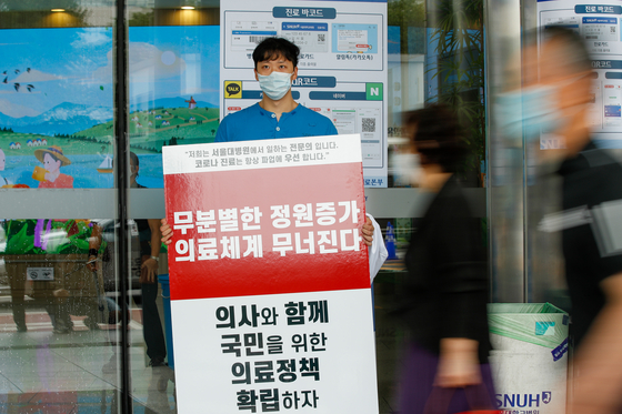 "A trainee doctor stages a one-man rally Monday at the Seoul National University Hospital (SNUH) in central Seoul and holds up a picket protesting the government's plan to increase medical school admissions, saying it will lead to the ""collapse of the health care system."" [NEWS1]"