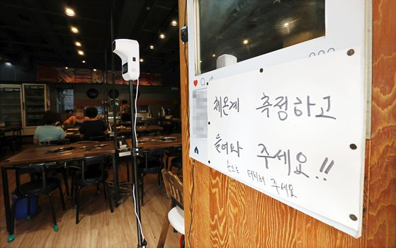 An automatic body temperature thermometer is installed at a restaurant in downtown Seoul on Aug. 28. [YONHAP]