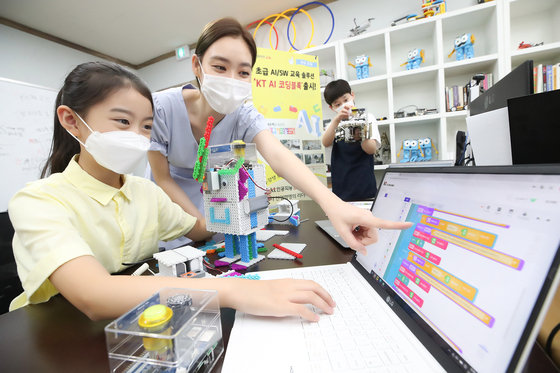 """Models pose in front of a laptop. KT on Monday said it introduced """"AI Coding Block,"""" which is an upgraded version of """"Genie Block,"""" a coding training platform made available in September last year. [YONHAP]"""