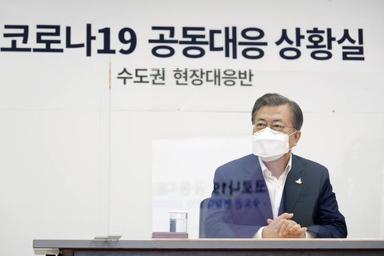 President Moon Jae-in listens to a briefing from officials of the National Medical Center at the hospital on Friday on the provision of sickbeds for serious cases of new coronavirus infection in the Seoul metropolitan area.  [YONHAP]