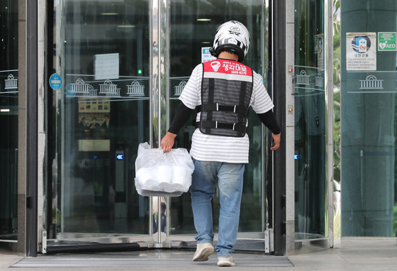 A delivery man takes food into the National Assembly compound in Yeouido, western Seoul, on Tuesday. Since Level 2.5 social distancing measures were imposed, many people prefer to order food instead of going to restaurants. [NEWS1]