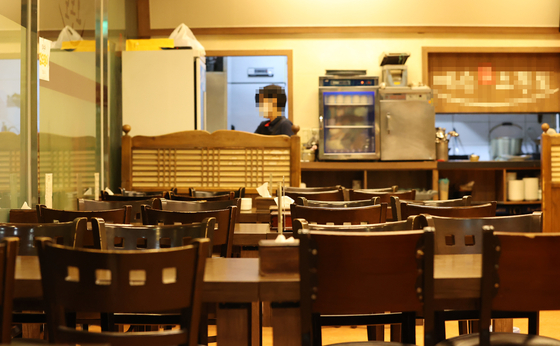 An empty restaurant in Jongno District, central Seoul, on Tuesday. The number of customers at restaurants has declined following the implementation of stricter regulations on the food service industry that started taking effect Sunday. [YONHAP]