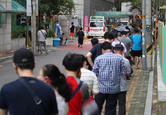 People line up at a Covid-19 testing site in Guro District, western Seoul, Thursday, where eight people from the same apartment building tested positive for the virus. [YONHAP]