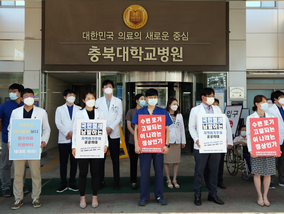 Professors at Chungbuk National University Hospital in Cheongju, North Chungcheong, show support for striking trainee doctors Tuesday after residents and interns tendered their resignations to protest the government's medical reform plans. [YONHAP]