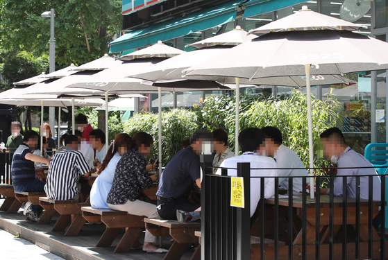 Customers drink at tables outside a convenience store in central Seoul on Tuesday. [YONHAP]