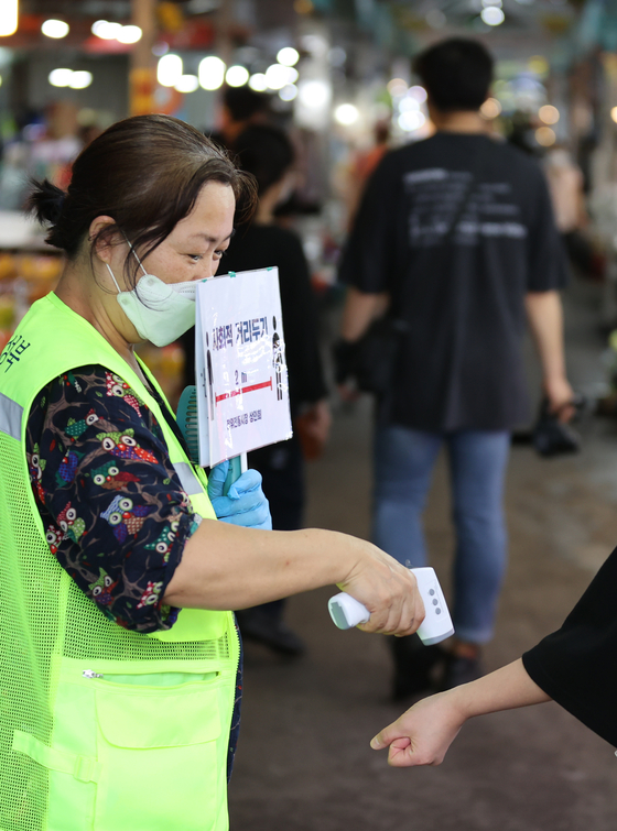 A visitor to Jangwi Traditional Market in Seongbuk District, central Seoul, gets their temperature checked at the entrance on Wednesday. The market is near the Sarang Jeil Church, blamed for the current spike in coronavirus cases. [YONHAP]