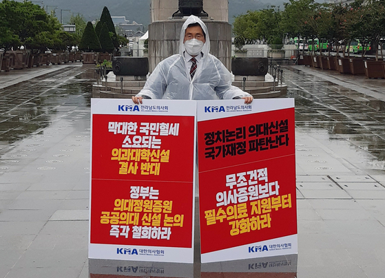 """Lee Pil-soo, president of the Jeollanamdo Medical Association and vice president of the Korea Medical Association (KMA), stages a one-man rally in Gwanghwamun Square in central Seoul Wednesday, urging the government to scrap its plans to expand medical school admissions and holding a sign saying, 'Doctors are citizens too."""" [YONHAP]"""