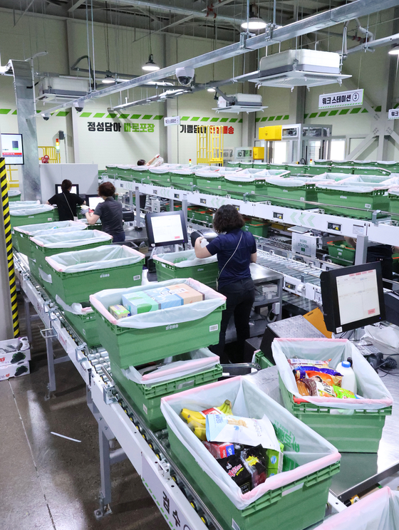 Employees prepare packages on Tuesday in a fulfillment center at the Junggye branch of Lotte Mart in Nowon District, northern Seoul. Online food delivery is shooting up after the initiation of heightened social distancing measures in the metropolitan region. The Lotte Mart branch has been providing a two-hour delivery service since the end of April, which has led to an increase in sales. [YONHAP]