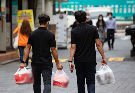 Office workers carry delivery food in Myeong-dong, central Seoul, on Aug. 31. [NEWS1]