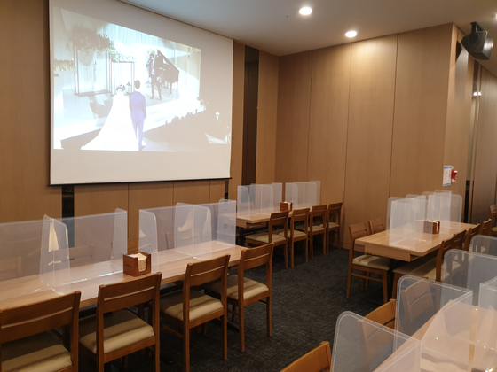 A real-time display of the wedding plays on a large screen on Sunday at the banquet hall of a wedding venue in Seoul. Since the initiation of Level 2 social distancing, all buffet services have stopped. [JEONG JIN-HO]
