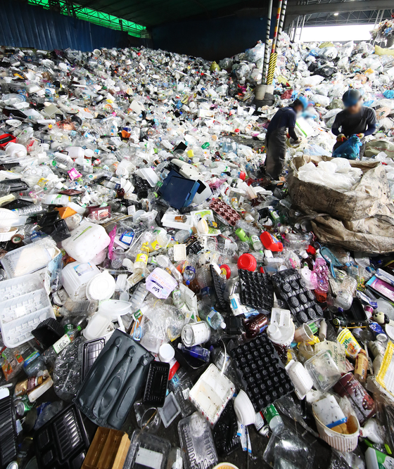Employees at a recycling center in Yongin, Gyeonggi, sort out recyclable trash on Wednesday. The coronavirus pandemic has caused an increase of recyclable waste as more people order food and goods to be delivered rather than risk visiting brick-and-mortar stores. [YONHAP]