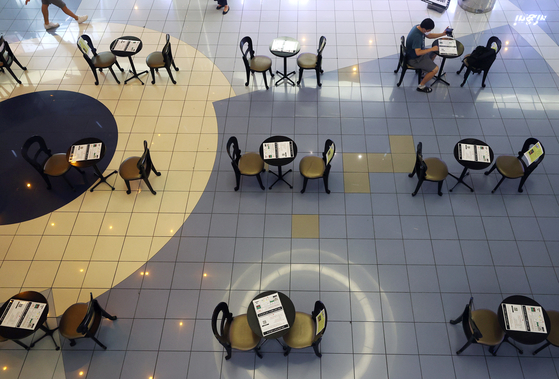 Tables are spaced out at a movie theater in downtown Seoul Wednesday, each with a pamphlet describing sanitation guidelines. [YONHAP]