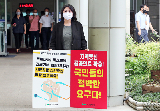 A member of the civic group Citizens' Solidarity for Participation of Busan holds a one-person picket protest in front of Busan City Hall, showing support for expanding regional health care services and urging doctors to halt their strike and return to treating patients amid the Covid-19 pandemic. [SONG BONG-GEUN]