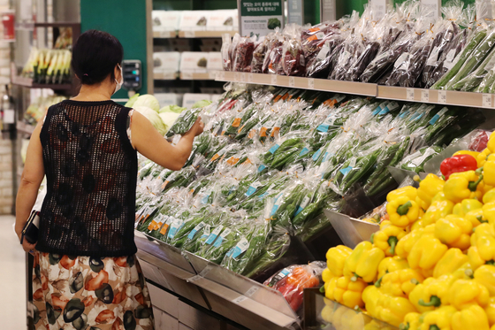 A shopper in the vegetable section of a discount mart in Seoul on Aug. 27. The longest streak of rainfall in August drove up vegetable prices. [YONHAP]