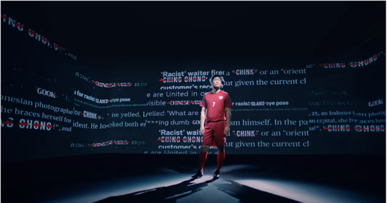 """Park Ji-sung stands in a room with racist slogans projected on the walls in a new """"Shoot For Love"""" video. [SCREEN CAPTURE]"""