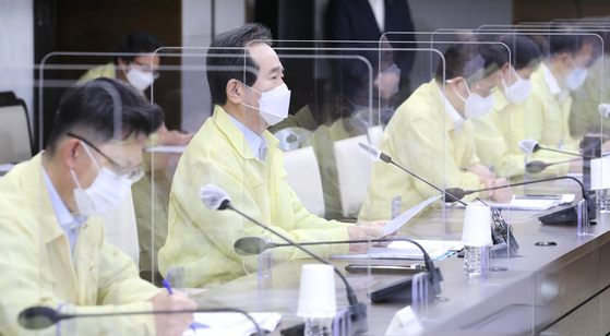 Prime Minister Chung Sye-kyun, second from left, presides over a Central Disaster and Safety Countermeasure Headquarters meeting on Wednesday from the Central Government Complex in Sejong City. In between participants are plastic dividers to prevent possible transmission of the coronavirus. [YONHAP]