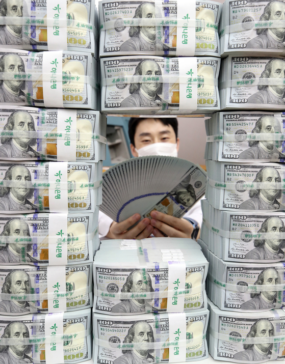 An employee poses with stacks of dollar bills at a Hana Bank branch in Jung District, central Seoul, on Thursday. According to data from the Bank of Korea (BOK), foreign exchange reserves came to $418.95 billion as of the end of August, up $2.4 billion from a month earlier. Korea's foreign exchange reserves have been increasing for five consecutive months. [YONHAP]