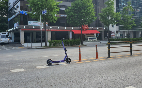 An electric scooter is parked at the center of a road in Songpa District, southern Seoul. [PARK MIN-JE]